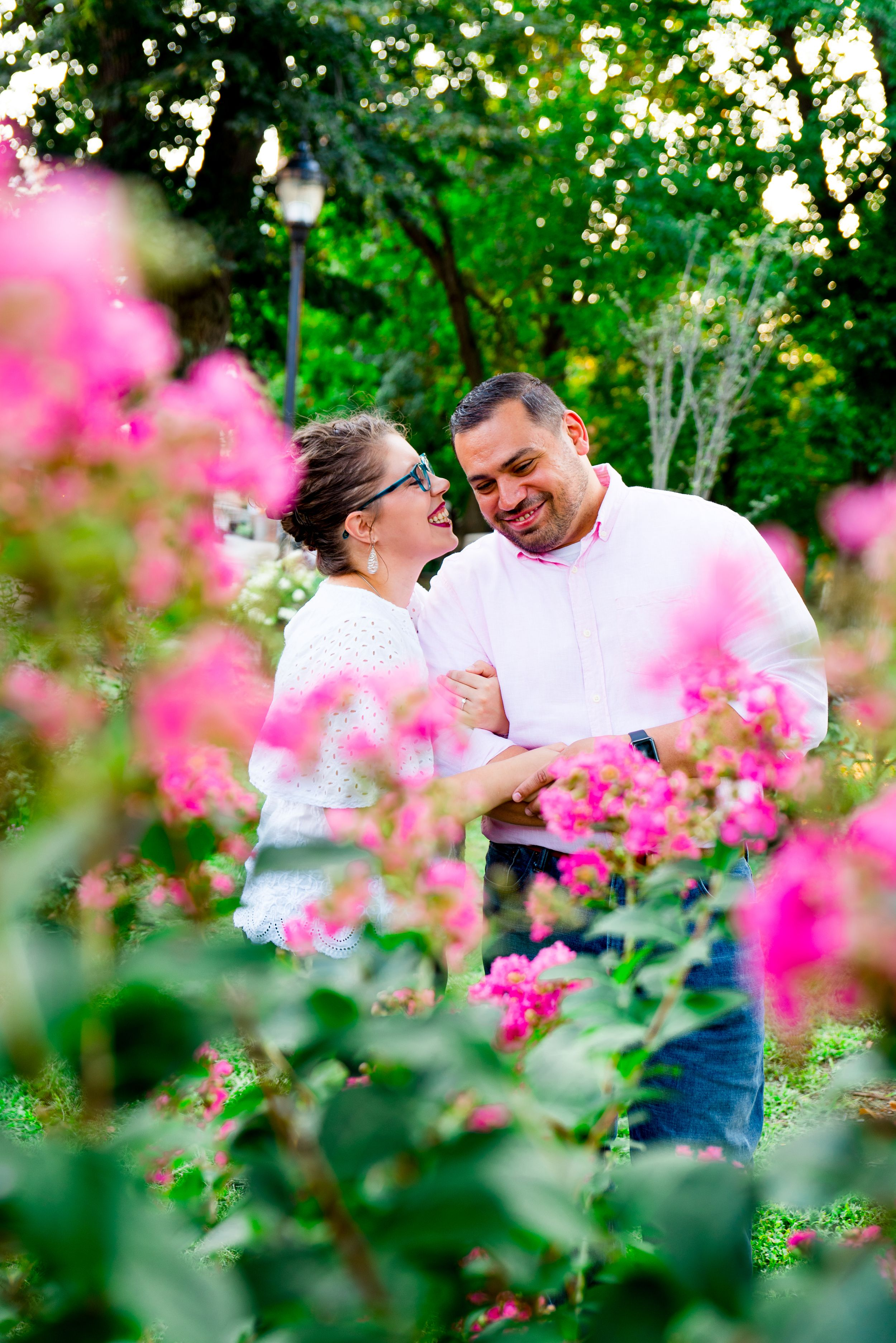 woman in white shirt and red lipstick pulls fiance in close to whisper in his ear and laughs behind a pink flower bush