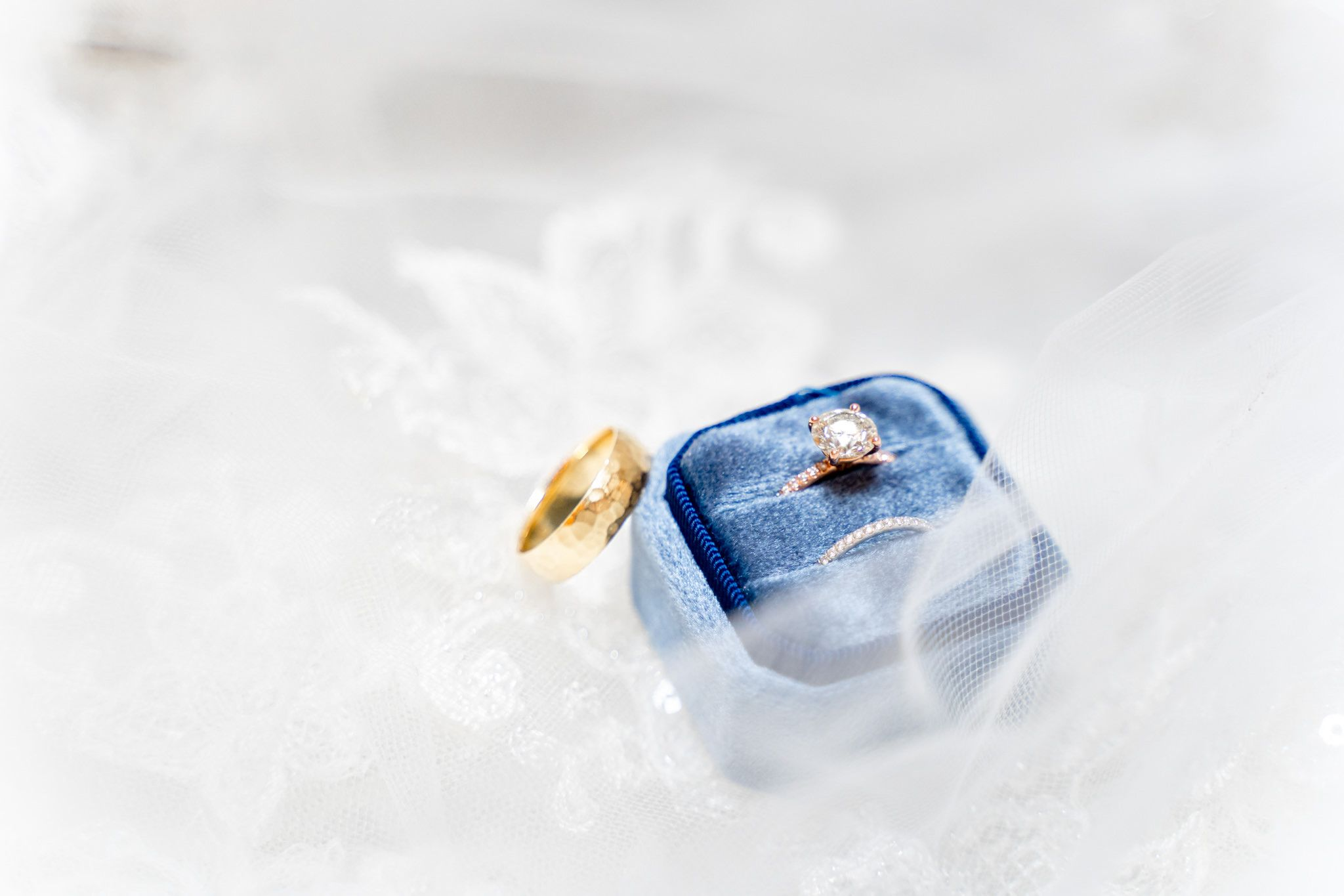 round diamond engagement ring with wedding bands in blue velvet ring box on lace wedding dress