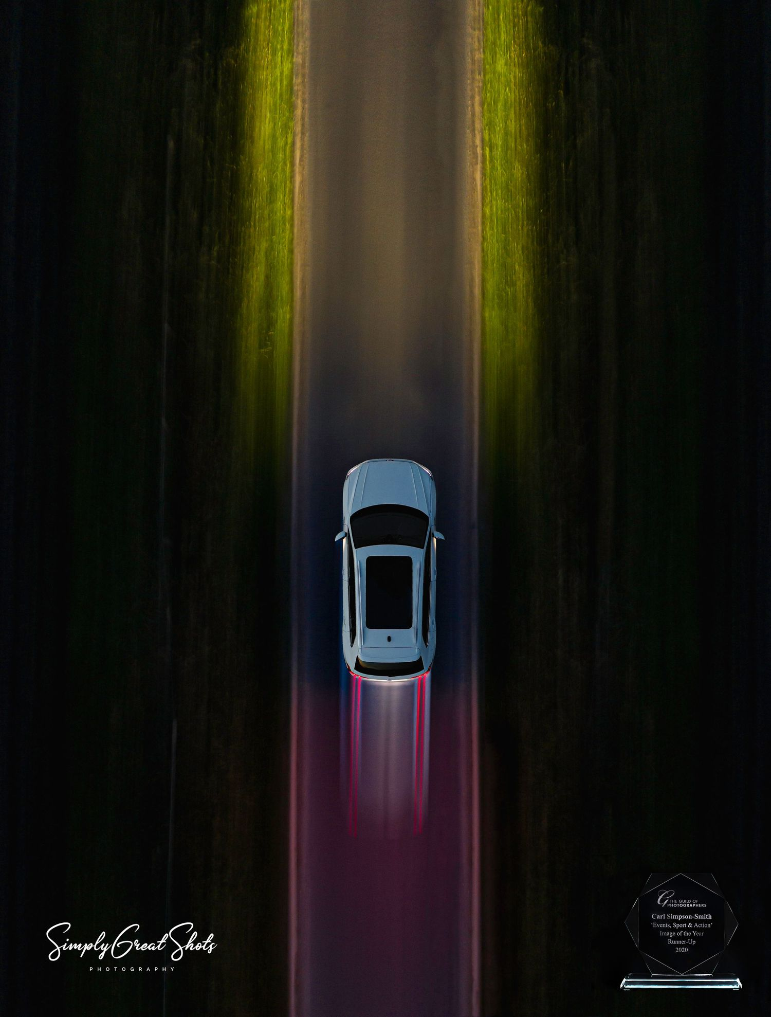 White car speeding down a country lane with light trails