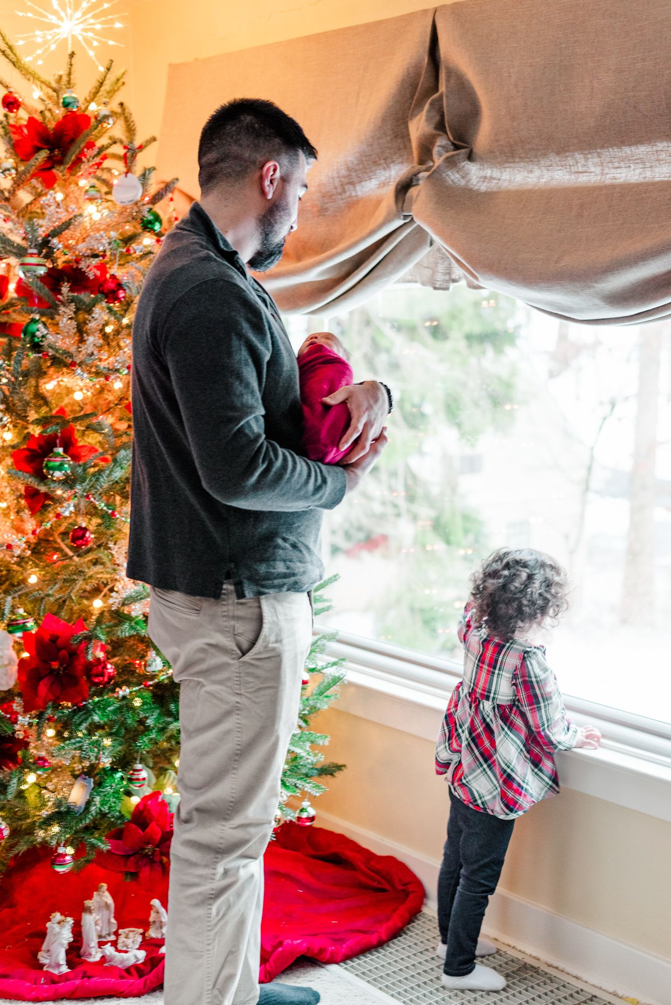Lifestyle father and big sister holding newborn baby in pink wrap in front of Christmas tree in Pittsburgh, Pennsylvania