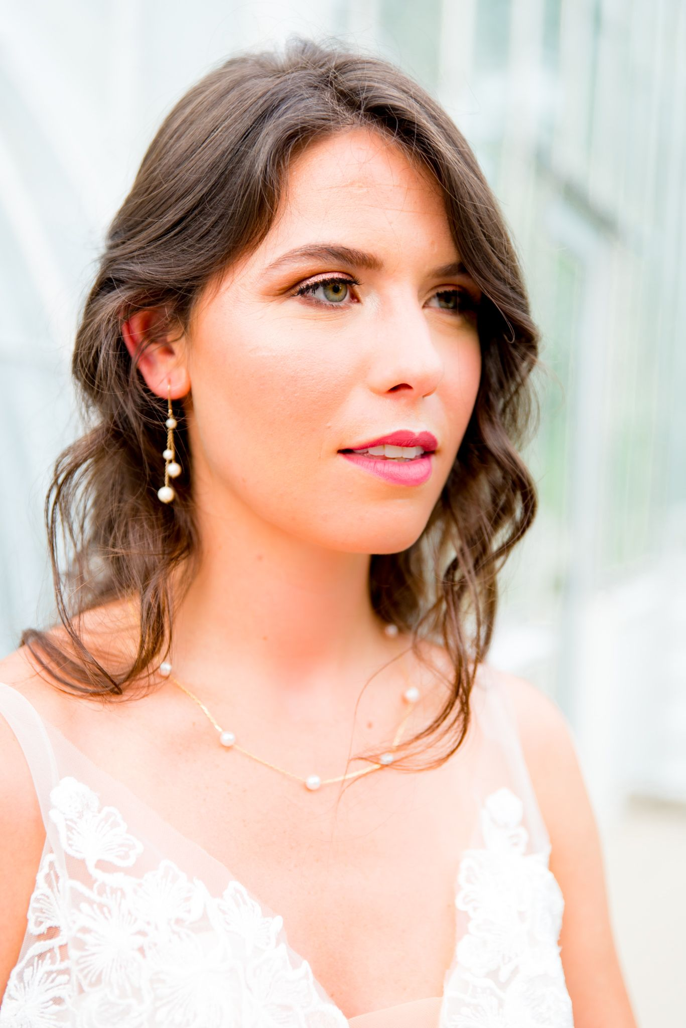 bride in hot pink lipstick, gold and pearl dangle earrings, and pearl and gold necklace stares off to the side at Krohn