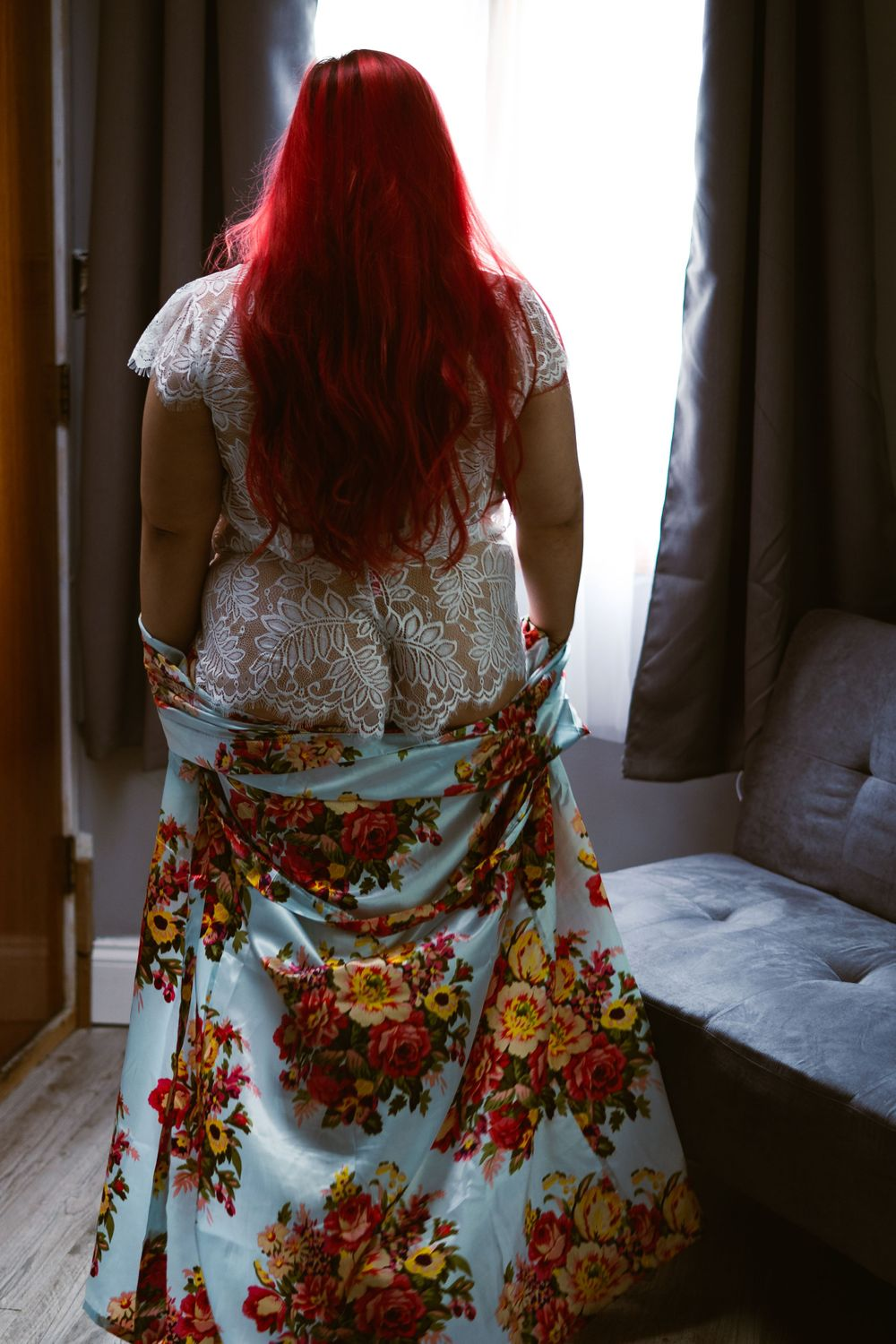 woman in bridal lingerie and floral bathrobe looking out the window, in a sexy pose with the robe framing her butt