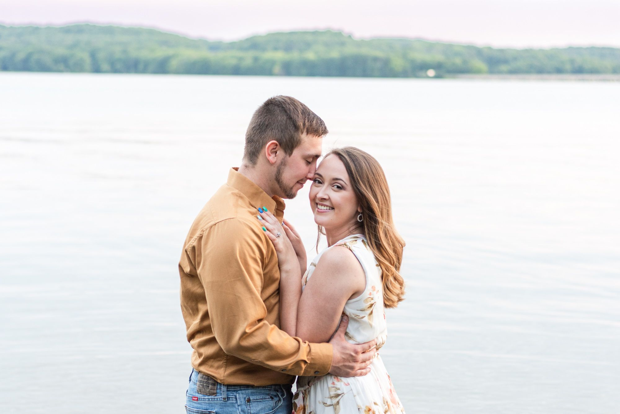 Couple holding each other in Lake Arthur for engagement at Moraine State Park in Pennsylvania