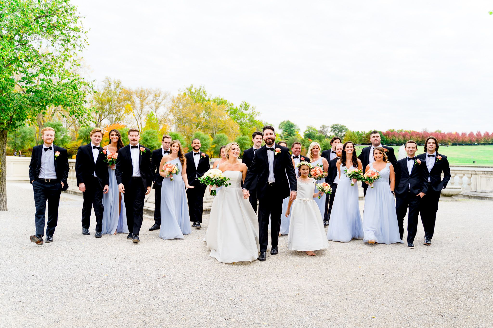 large wedding party in black suits and light blue dresses walk with bride and groom at Forest Park STL