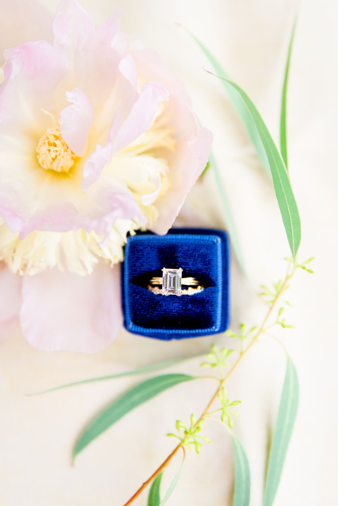 peony and green leaves surround blue ring box with emerald cut engagement ring and wedding band from Richter Phillips