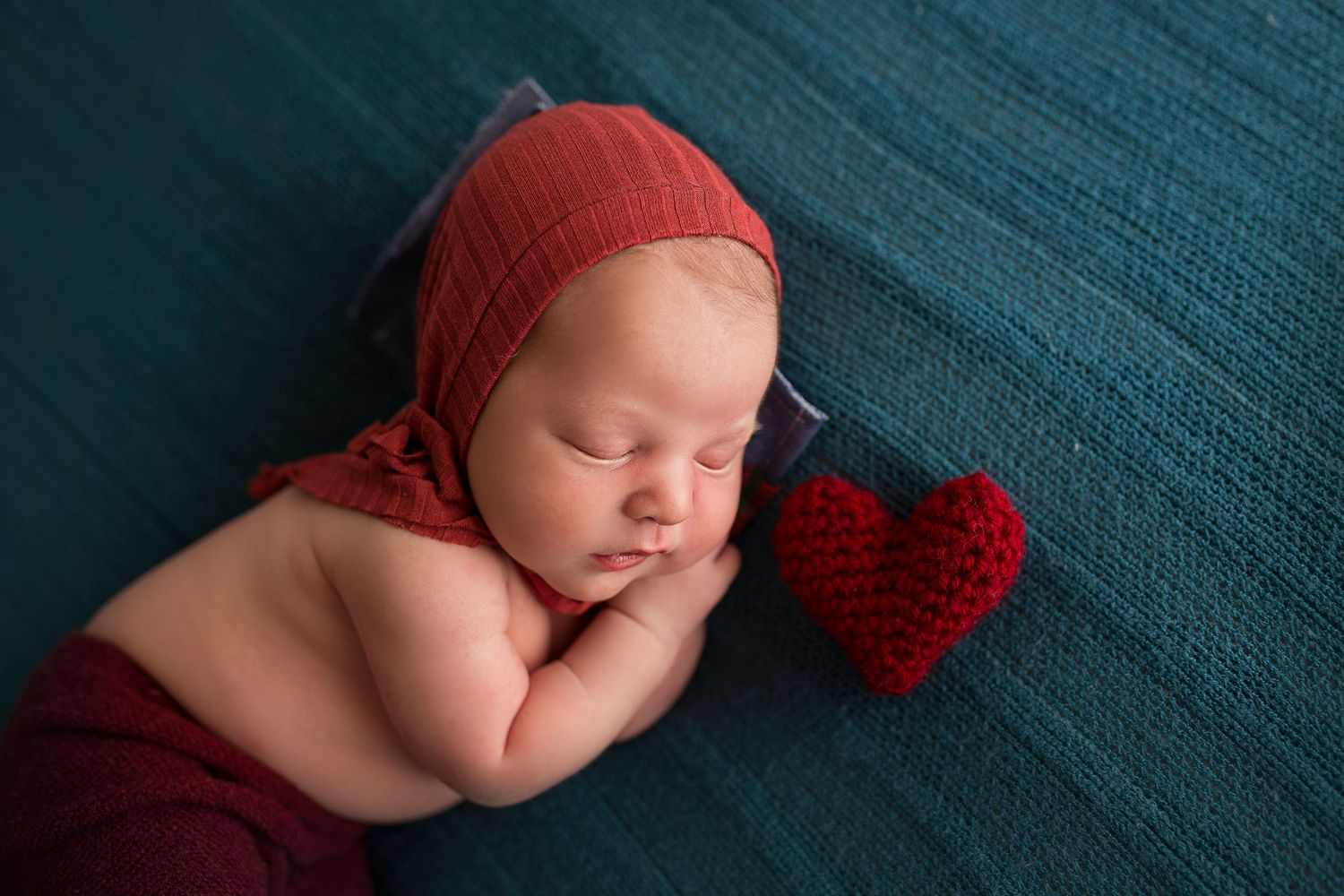 baby boy dressed in red with a knit heart