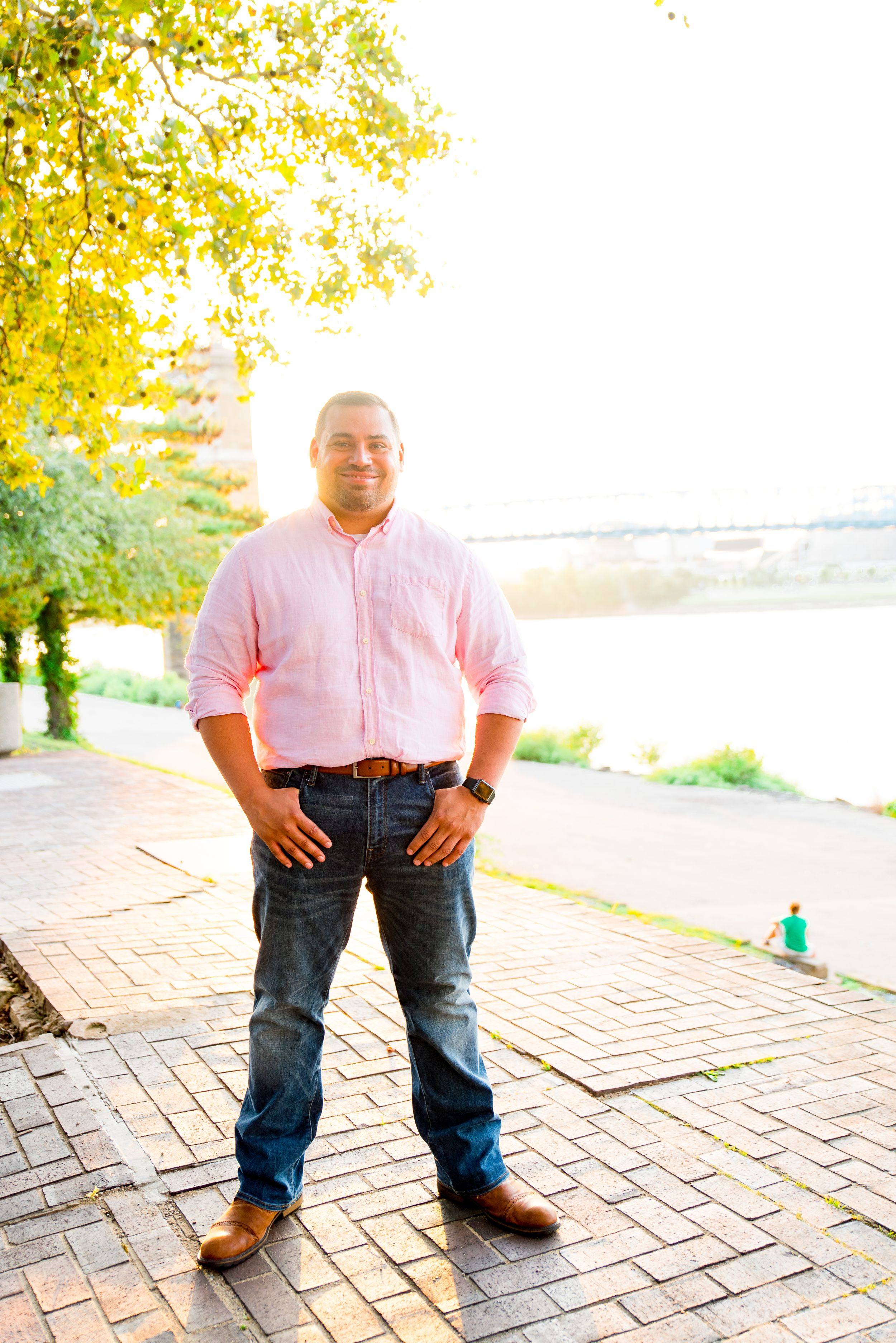 man in light pink long sleeve button down and dark blue jeans smiles in front of Roebling Bridge