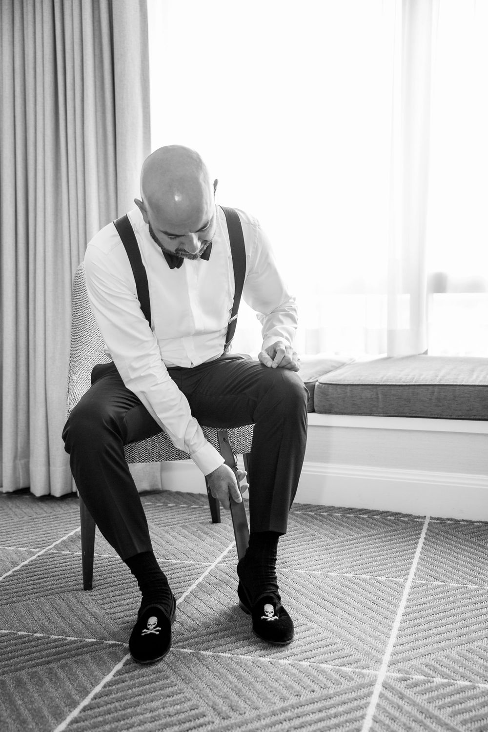 black and white groom putting shoes on