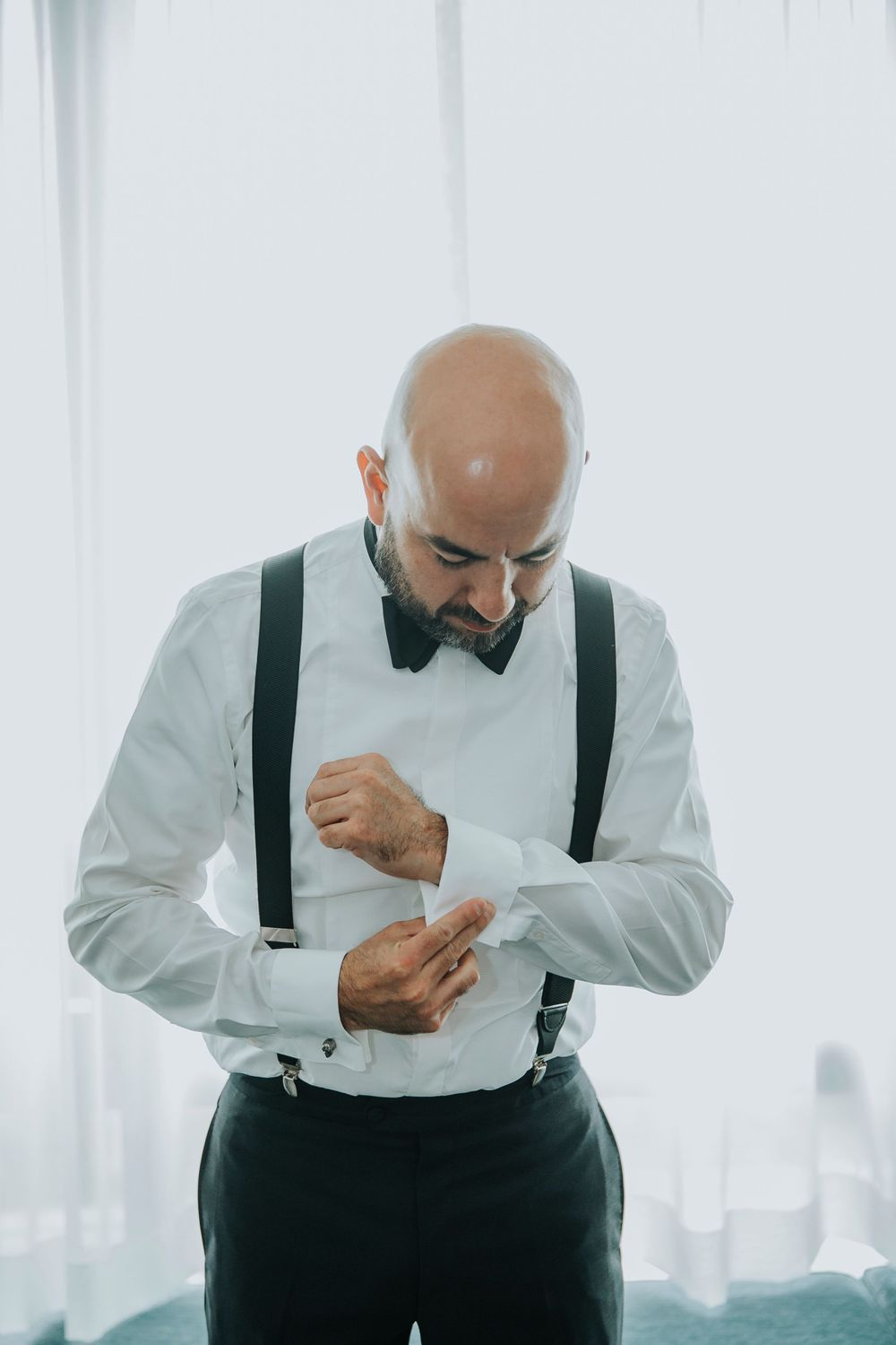 groom fixing cuff links while getting ready