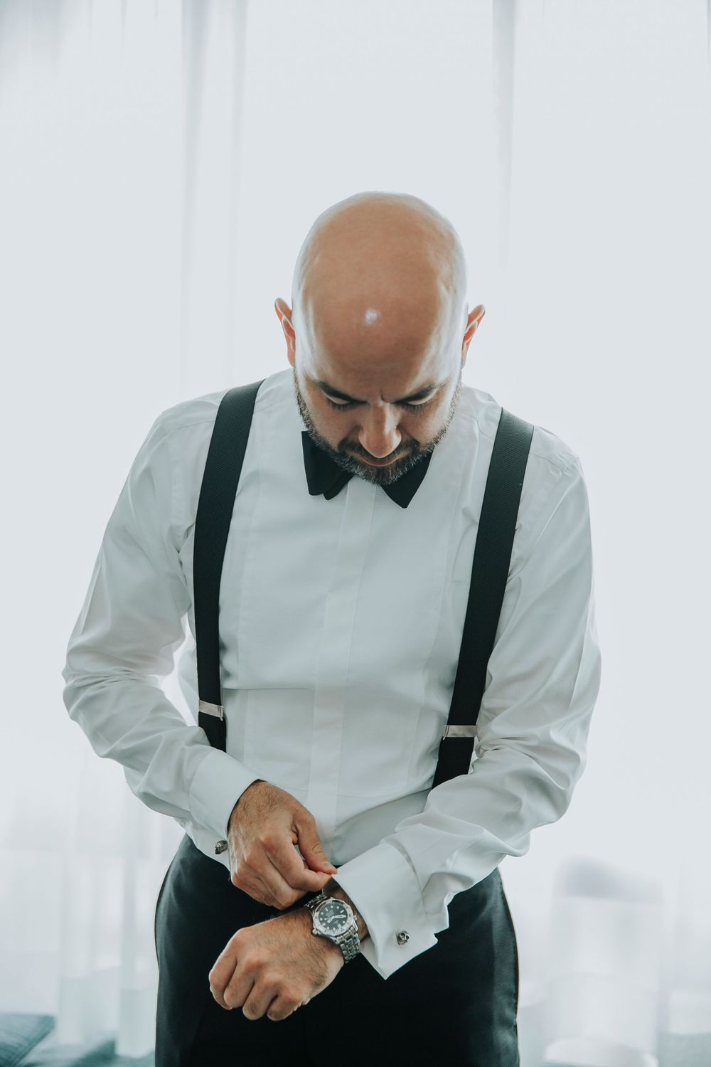 groom adjusting watch while getting ready