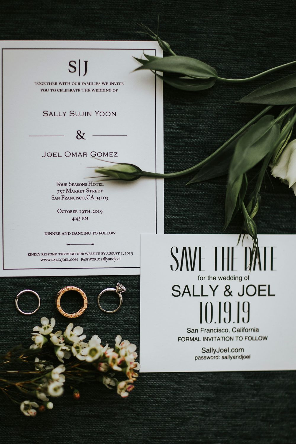 rings laying flat next to save the dates and wedding invites with flowers and greenery
