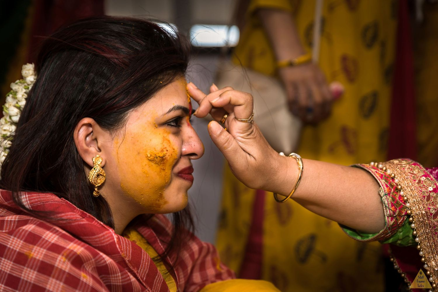 Relative putting tikka on bride's forehead on a haldi occasion
