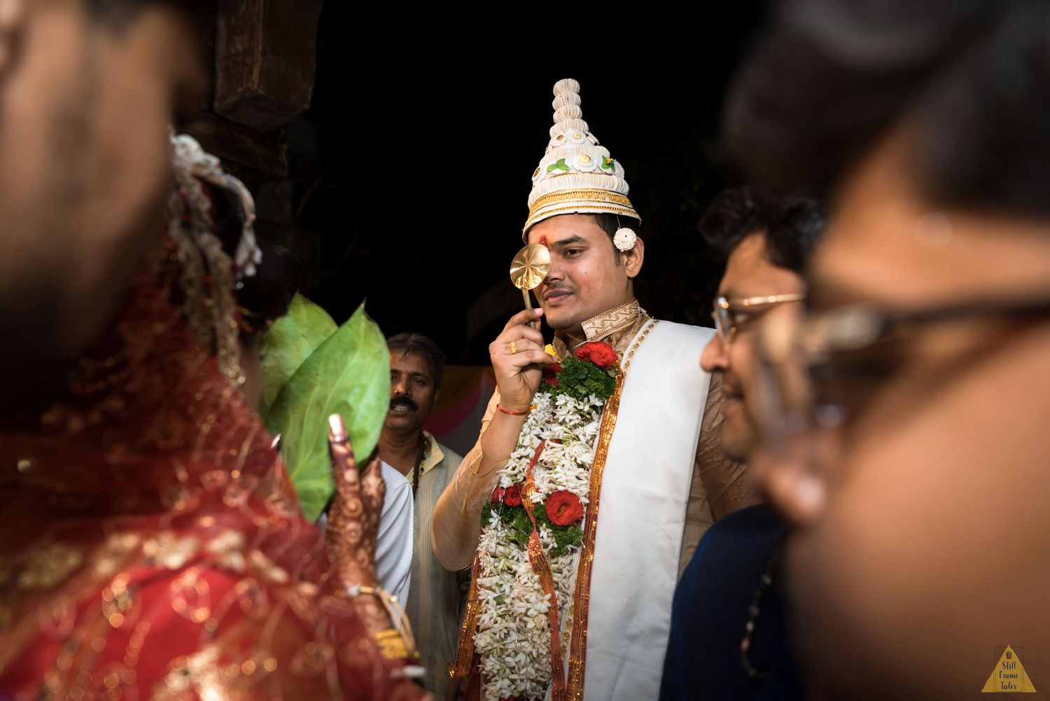 Groom holding spoon type object in front of his face in a begali wedding ritual