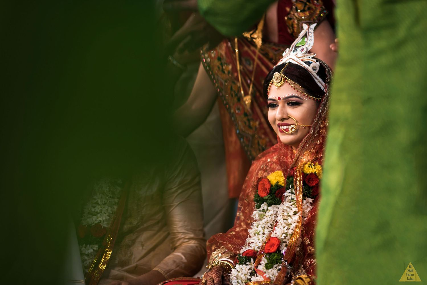 Bengali bride enjoying wedding day rituals in a green background=d