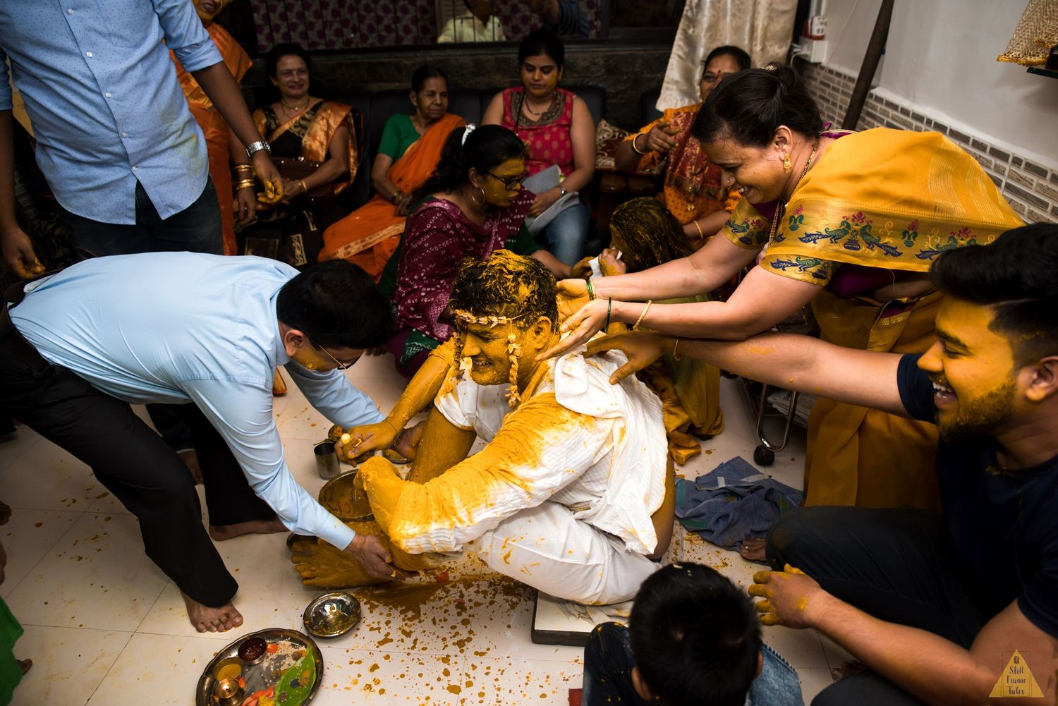 Family members painting groom in yellow haldi on wedding day