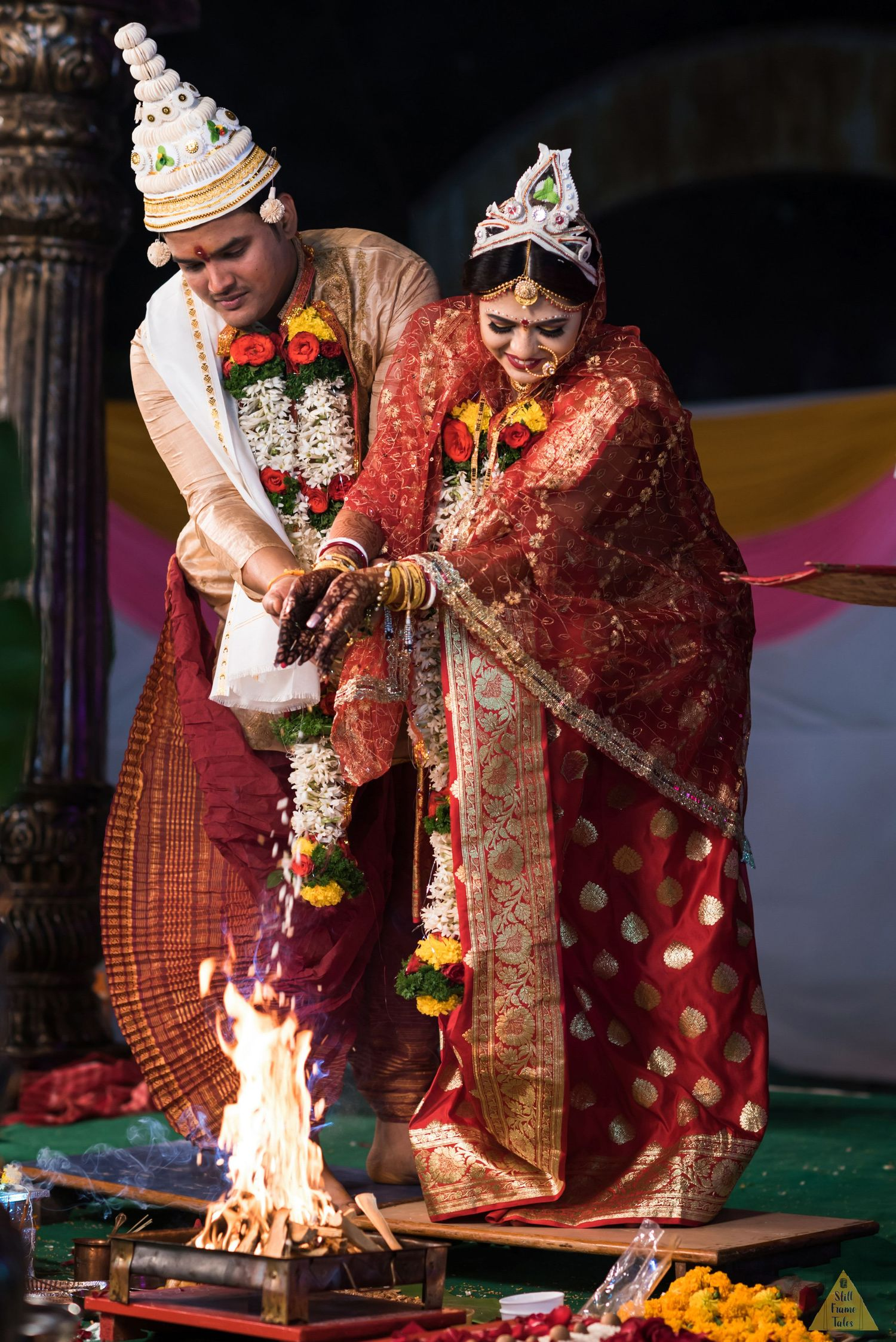 Indian couple performing feras on their wedding day along with hom puja