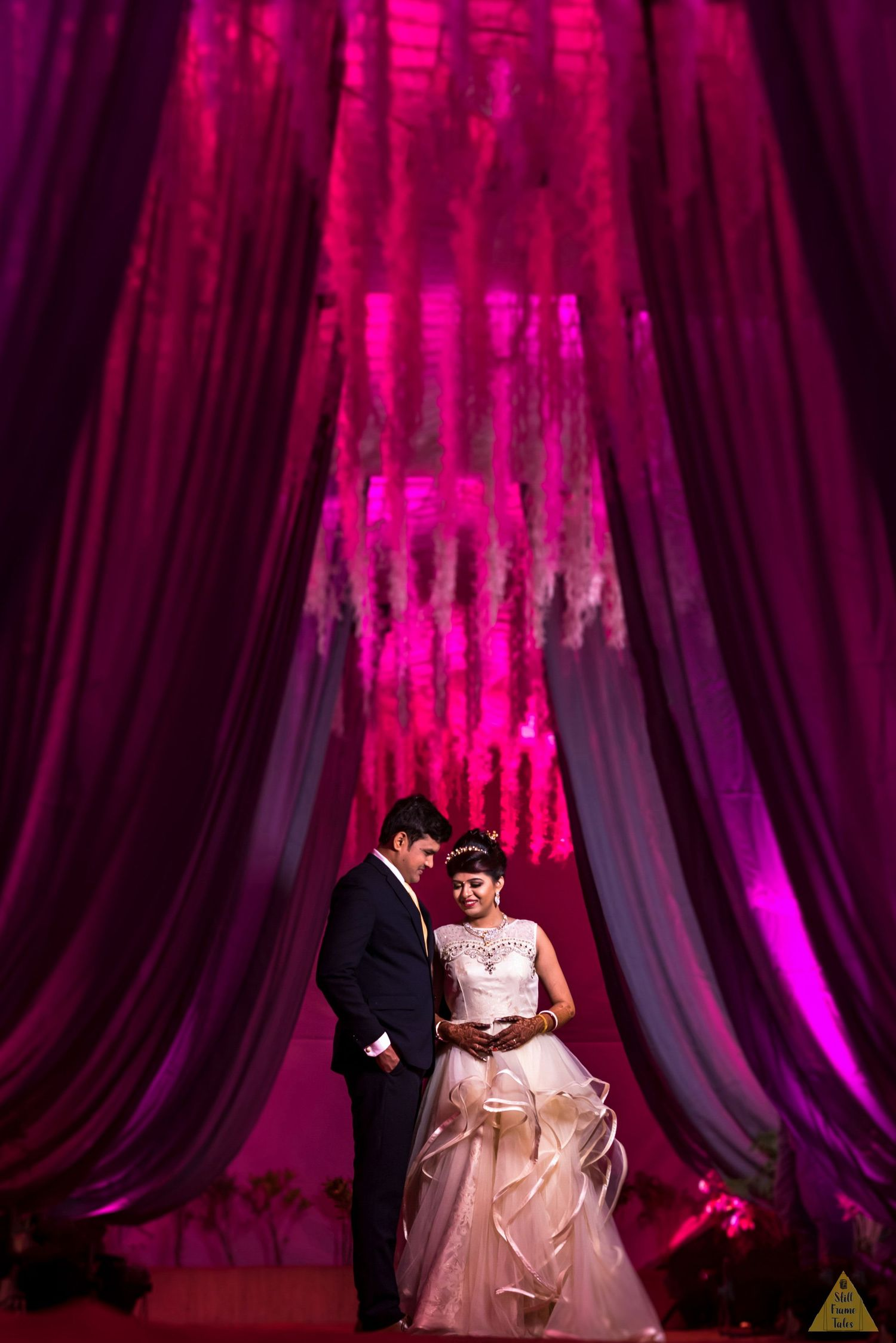 Elegant couple standing inside a pink tet background for their wedding day reception portrait