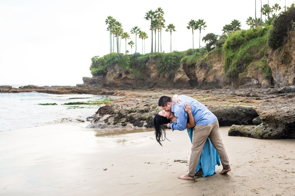 Image of a husband and wife kissing on the beach in Laguna Beach, CA