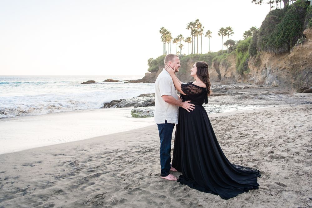 A pregnant woman and her husband standing on a beach in Laguna Beach, CA