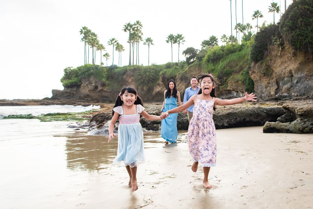 Image of two girls running on the beach in Laguna Beach, CA