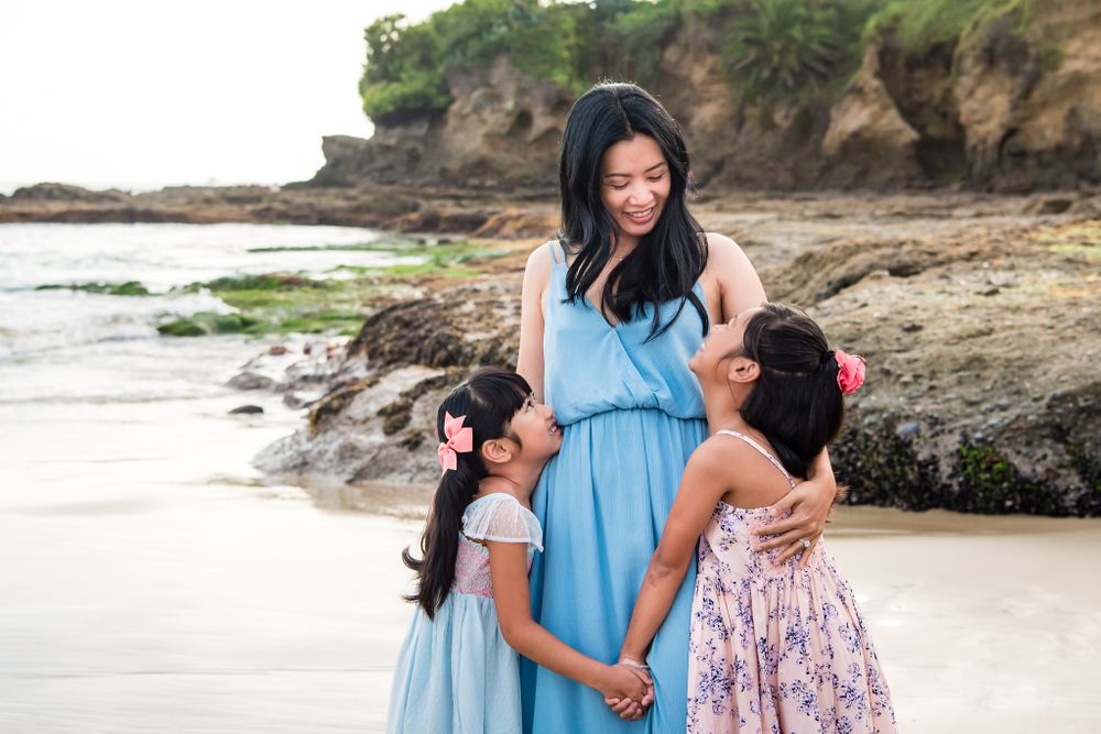 A photo of a mother and her daughters on a beach in Laguna Beach, CA