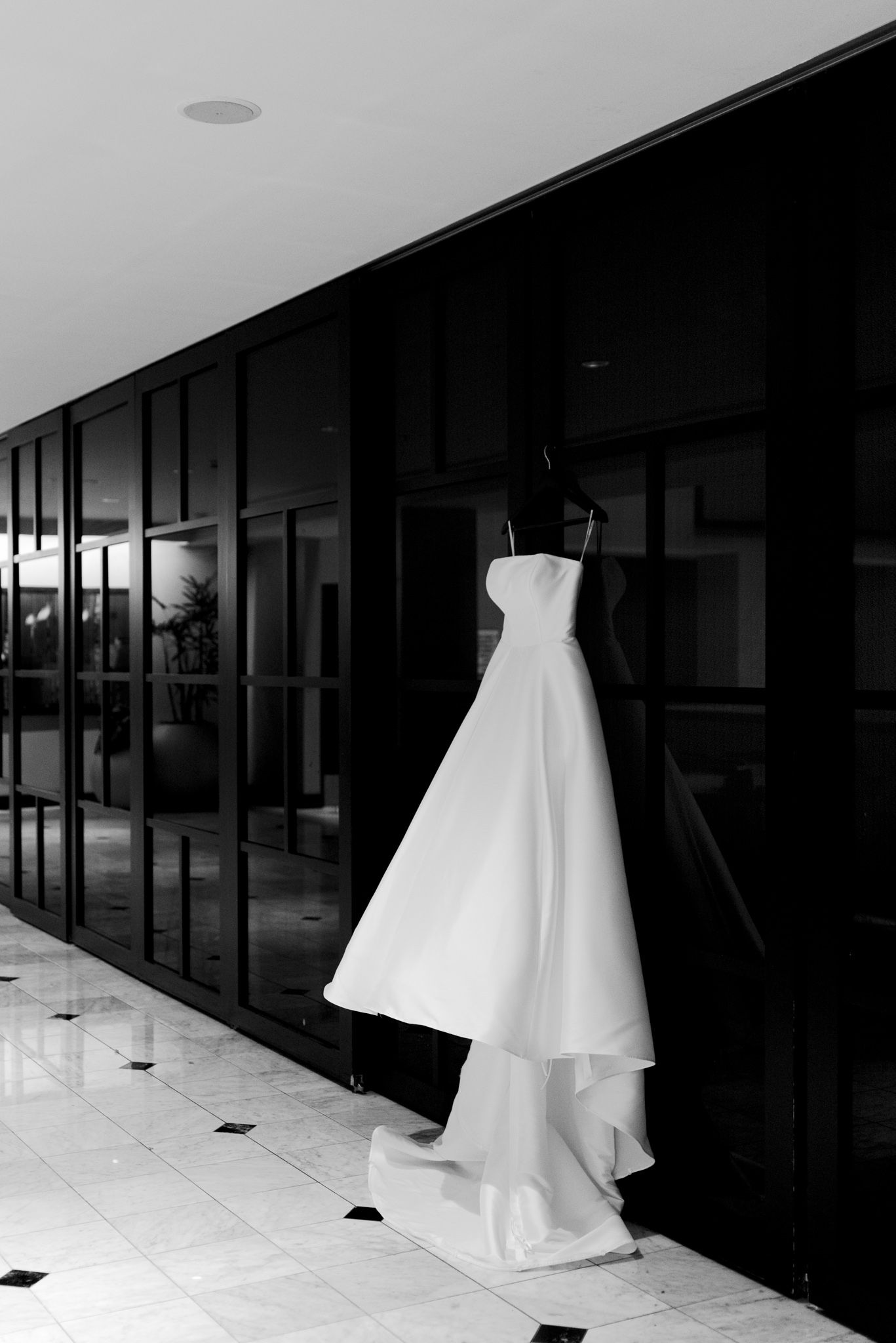 strapless wedding dress hanging on black doors for downtown St. Louis wedding