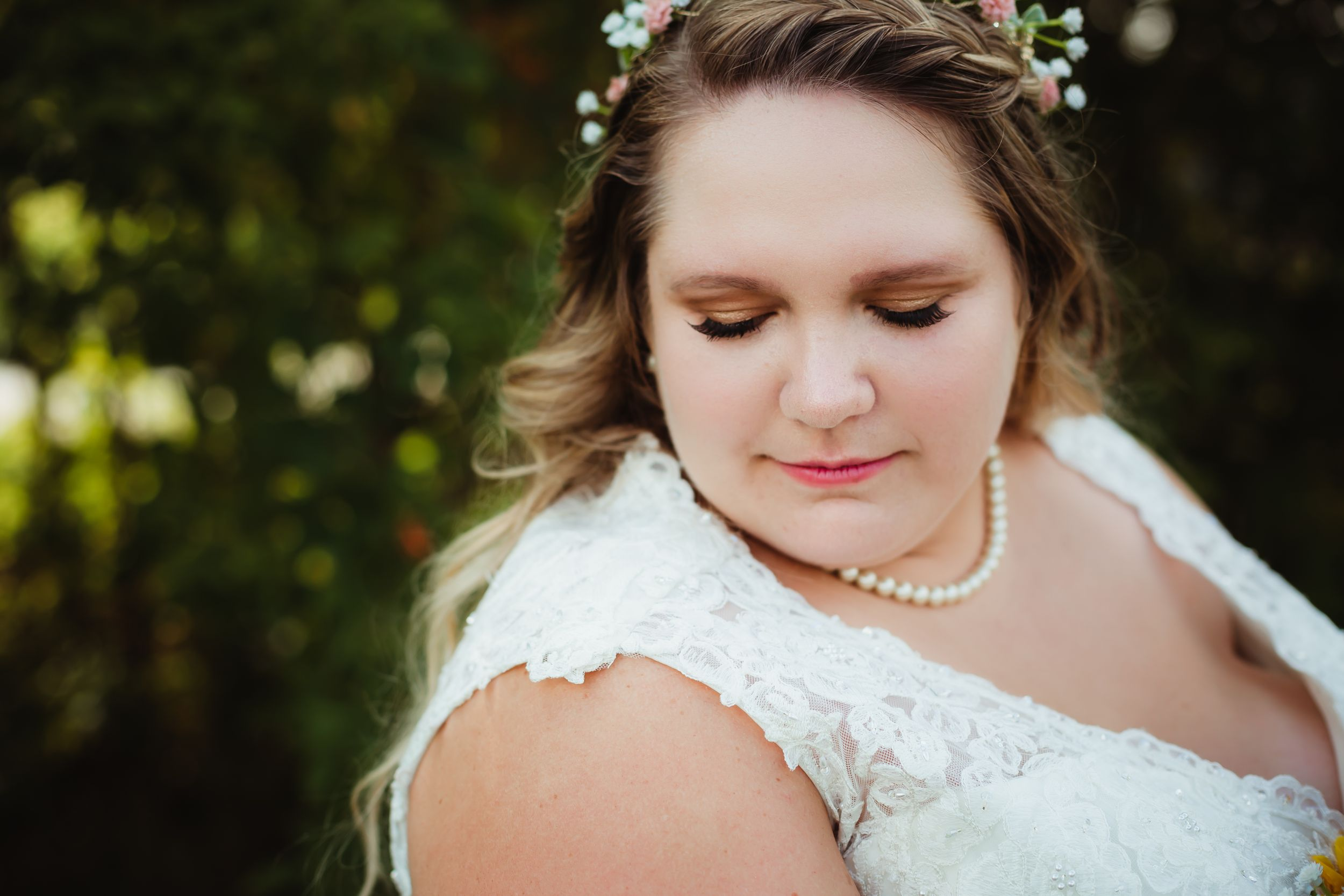 Close up of bride looking down at her shoulder. She has false eyelashes and a pearl necklace.