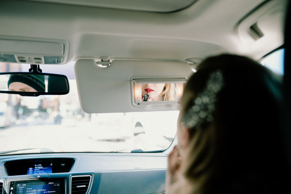 bride-putting-makeup-on-in-car-desmoines-iowa-raelyn-ramey-photography
