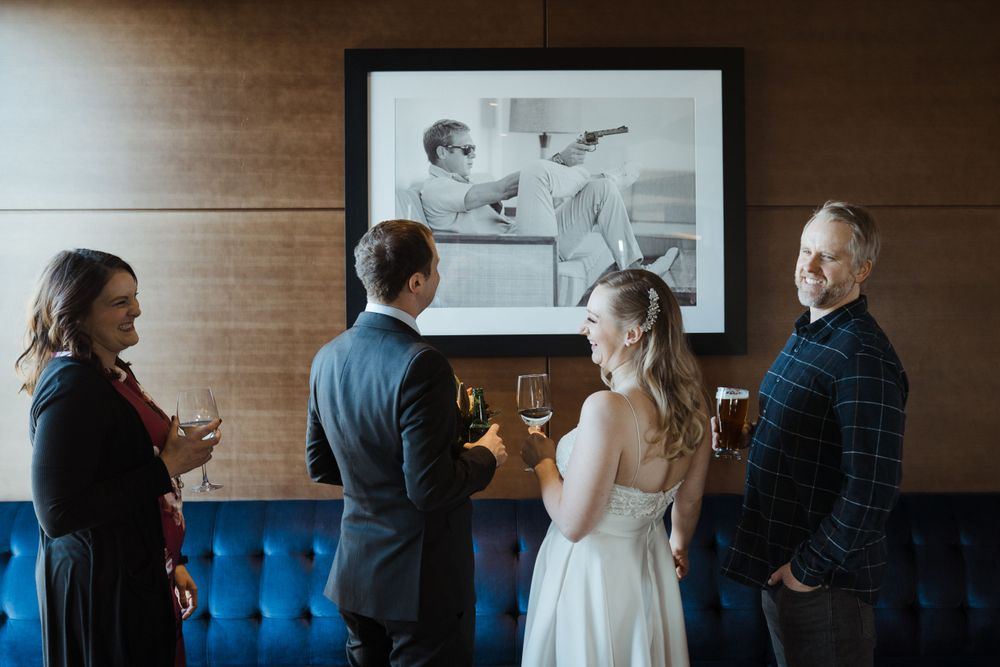 bride-groom-and-friends-talking-in-front-of-art-the-republic-on-grand-elopement-desmoines-iowa-raelyn-ramey-photography