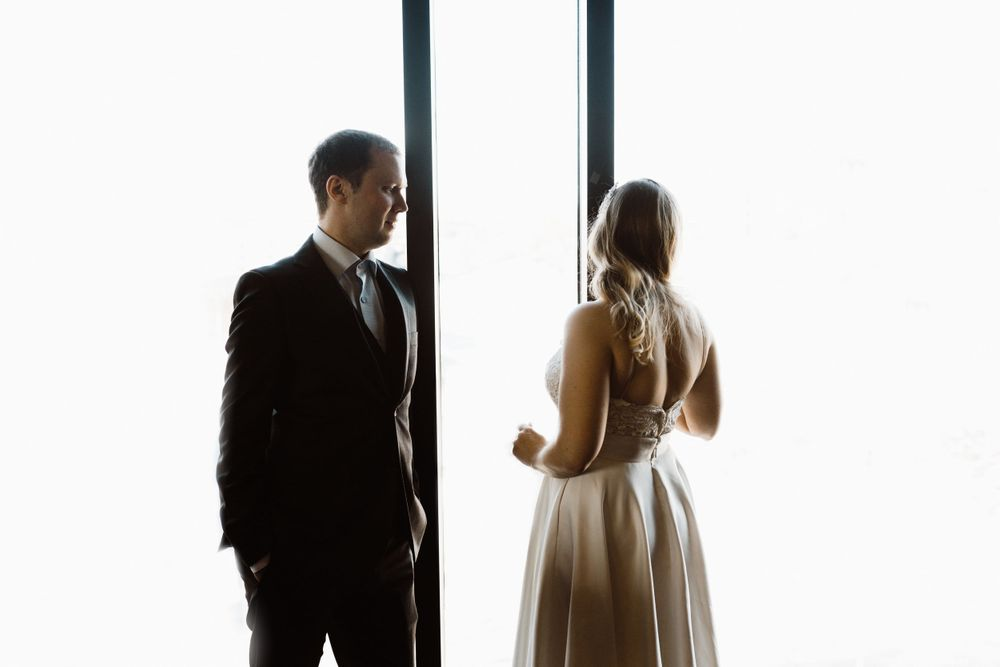 bride-groom-standing-in-front-of-windows-the-republic-on-grand-elopement-desmoines-iowa-raelyn-ramey-photography