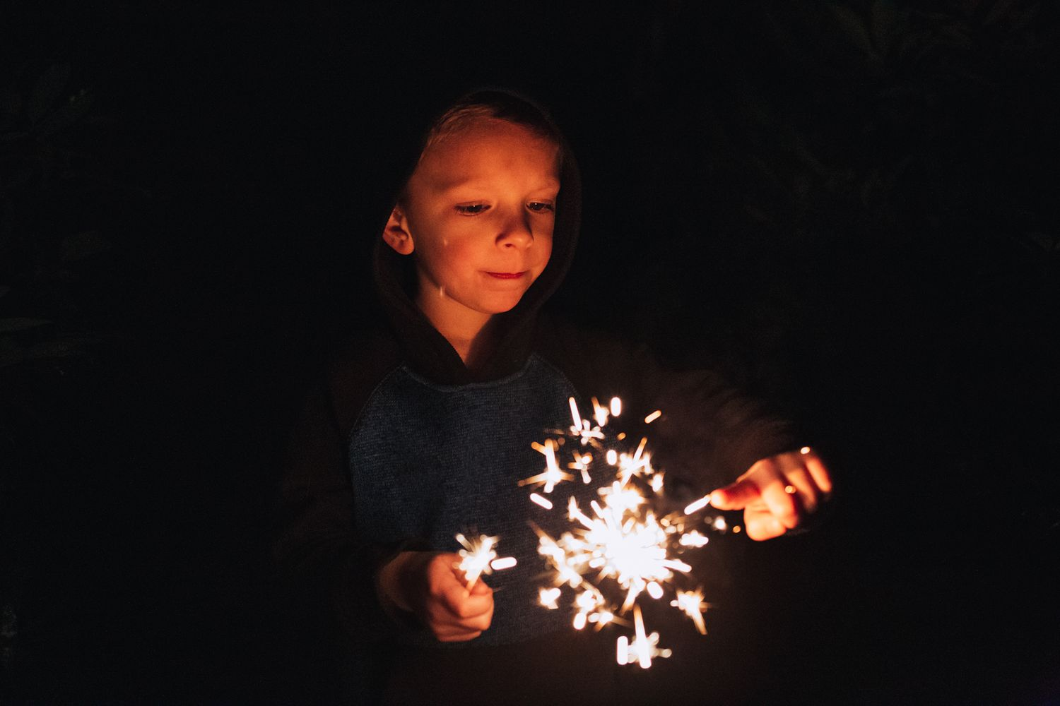 boy touching sparkler sparks on new years eve