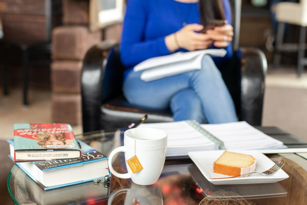 Lifestyle branding session in cafe with tea books and cake female business owner working on phone in Maple Valley, WA
