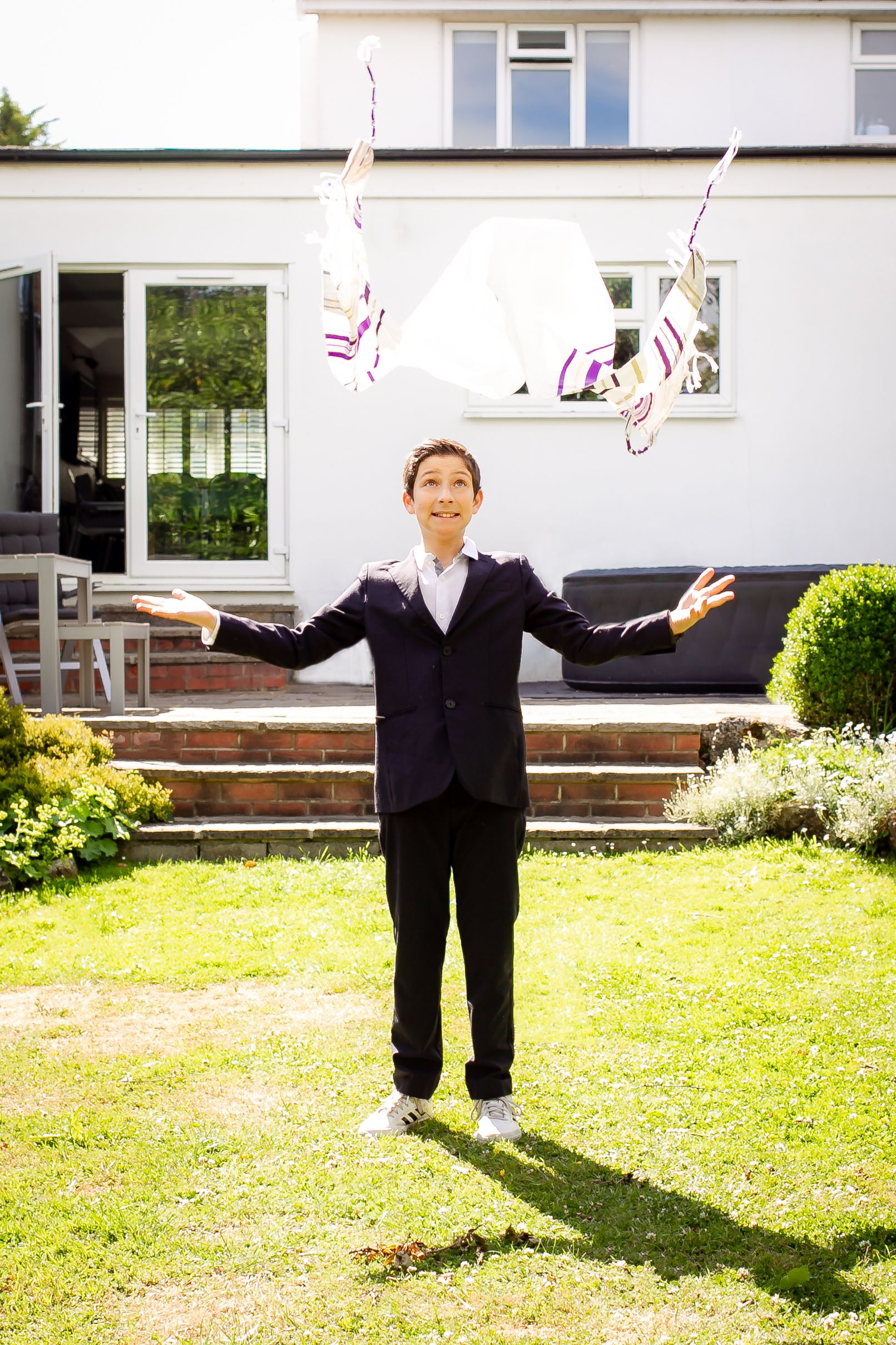 A Bar Mitzvah boy throws his tallis in the air in his garden - Bar Mitzvah Photography