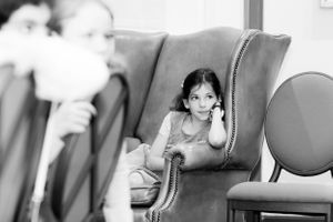 Little girl sits in a winged back armchair to listen to speeches at Allianz Park - Bar Mitzvah Photography