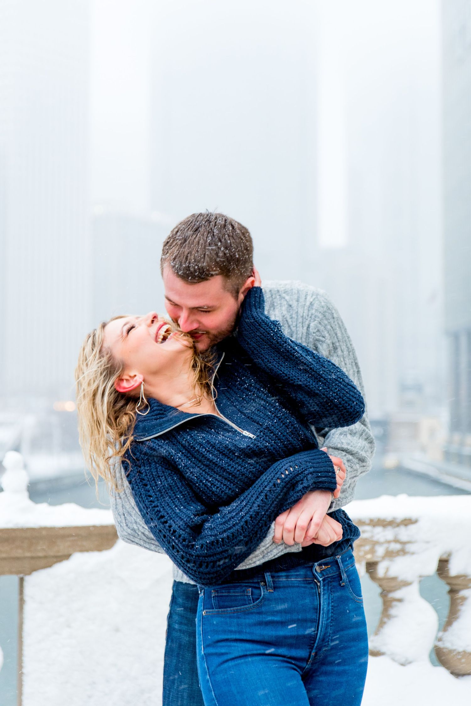 man in gray sweater hugging and kissing fiance in navy sweater at Wrigley Building for Chicago winter engagement picture
