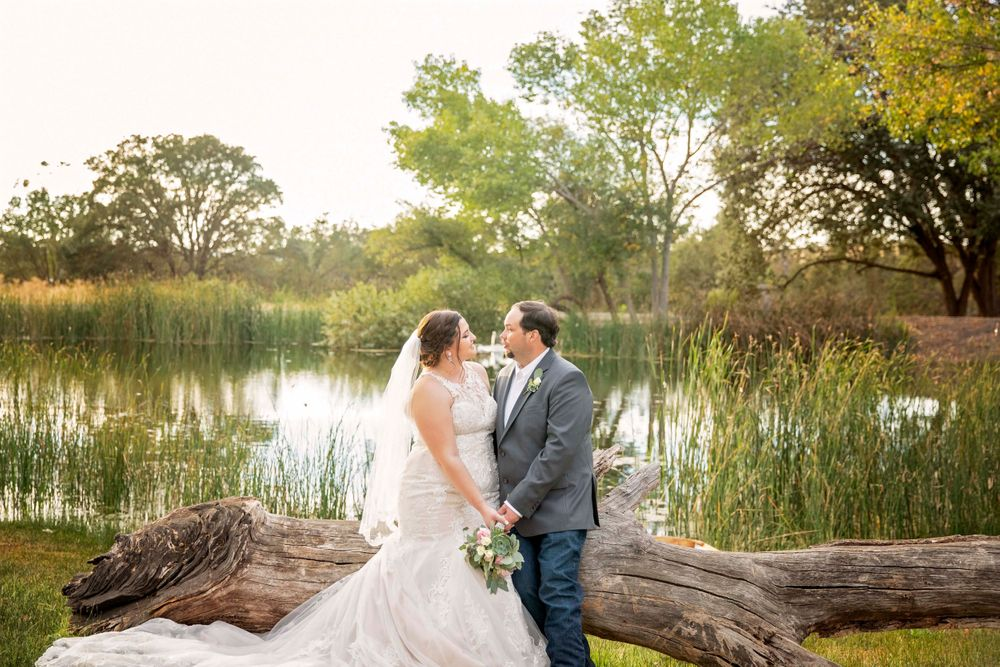 Bride and groom on a log at the pond at Fallen Oaks Estate