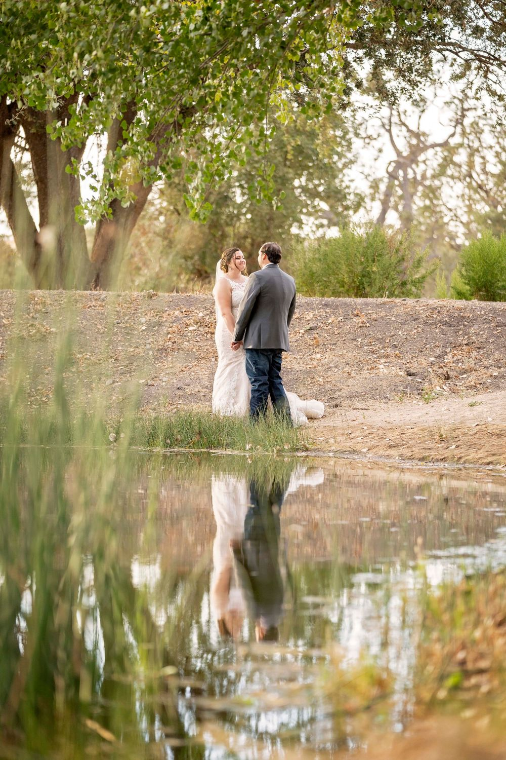 Bride and groom looking at each other with their reflection on the water at Fallen Oaks Estate