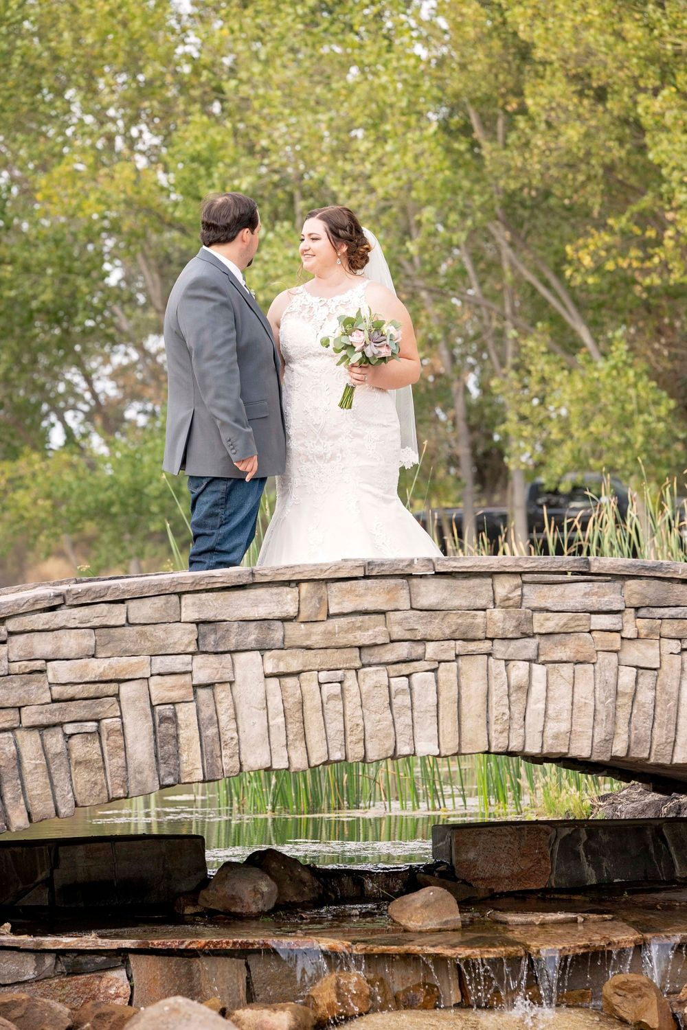 Bride and groom looking at each other on a bridge at Fallen Oaks Estate