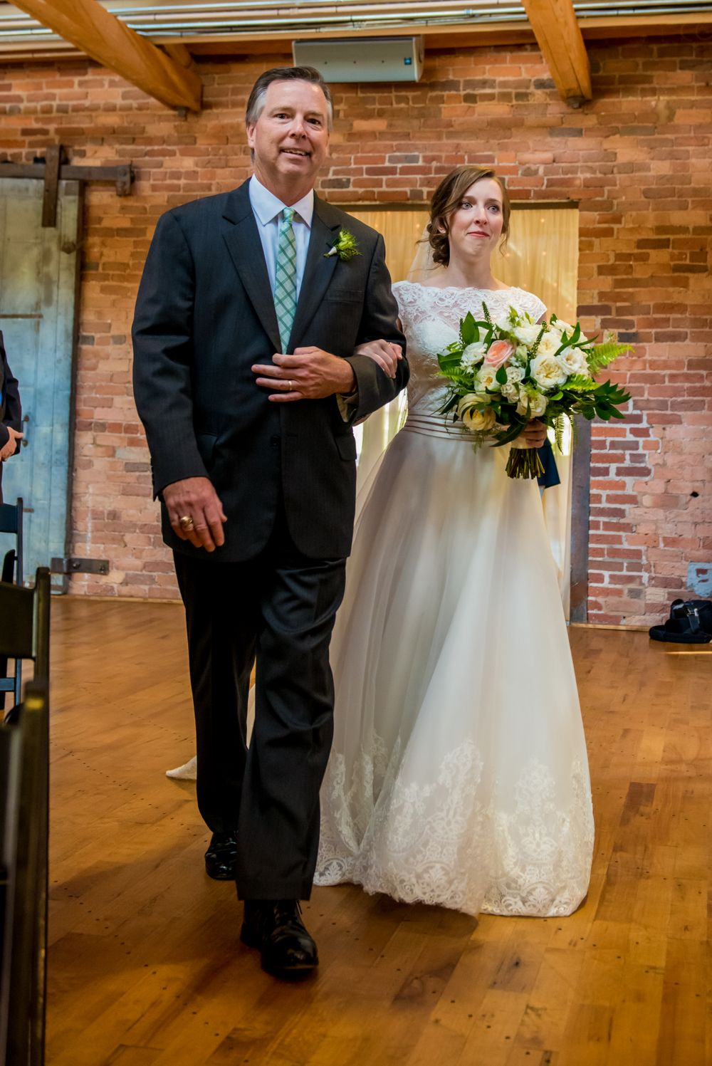 Bride Anna is walked down the aisle by her dad during her wedding at Certus Loft at the Huegonot Mill in Greenville, SC