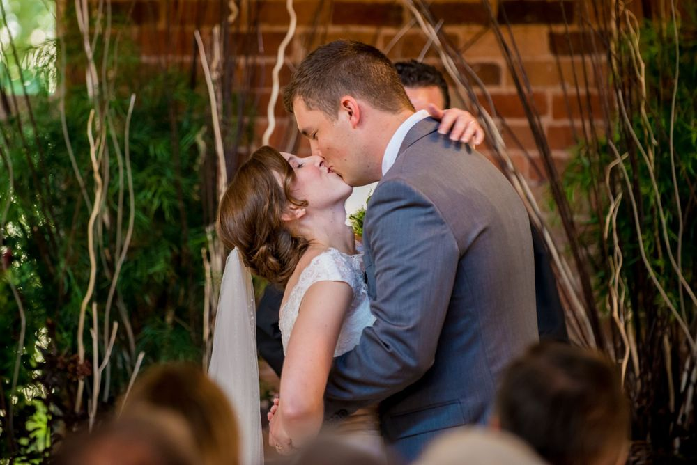 Bride Anna & Groom David have their first kis during their wedding at Certus Loft at the Huegonot Mill in Greenville SC