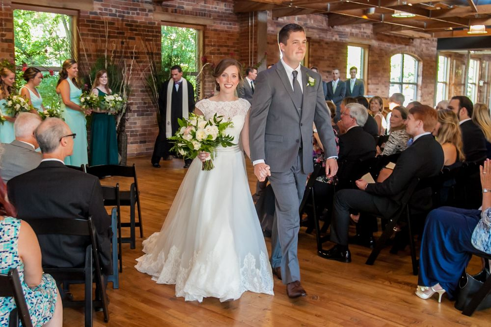 Anna and David walk down the aisle following their wedding at Certus Loft at the Huegonot Mill in Greenville, SC