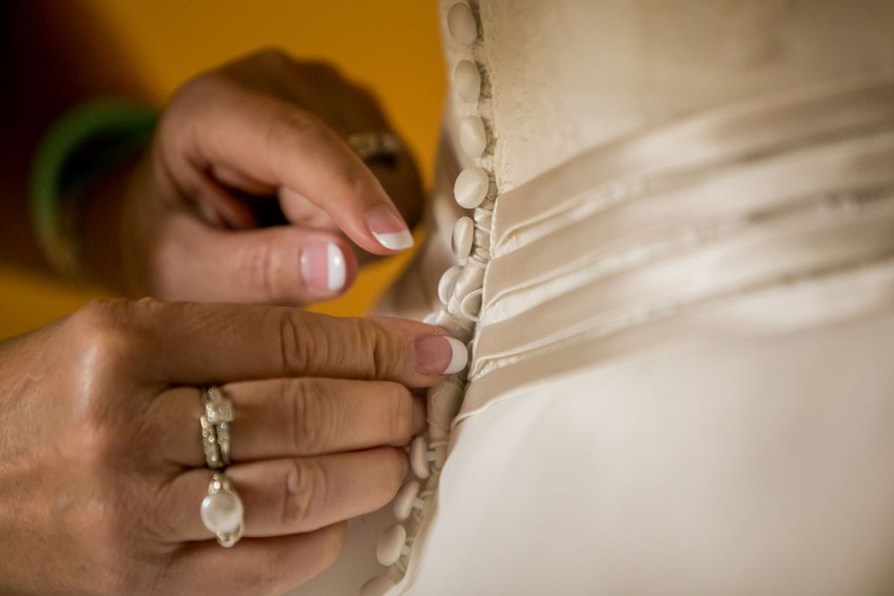Anna's mom buttons up the back of her bridal gown before her wedding at Certus Loft at the Huegonot Mill in Greenville,