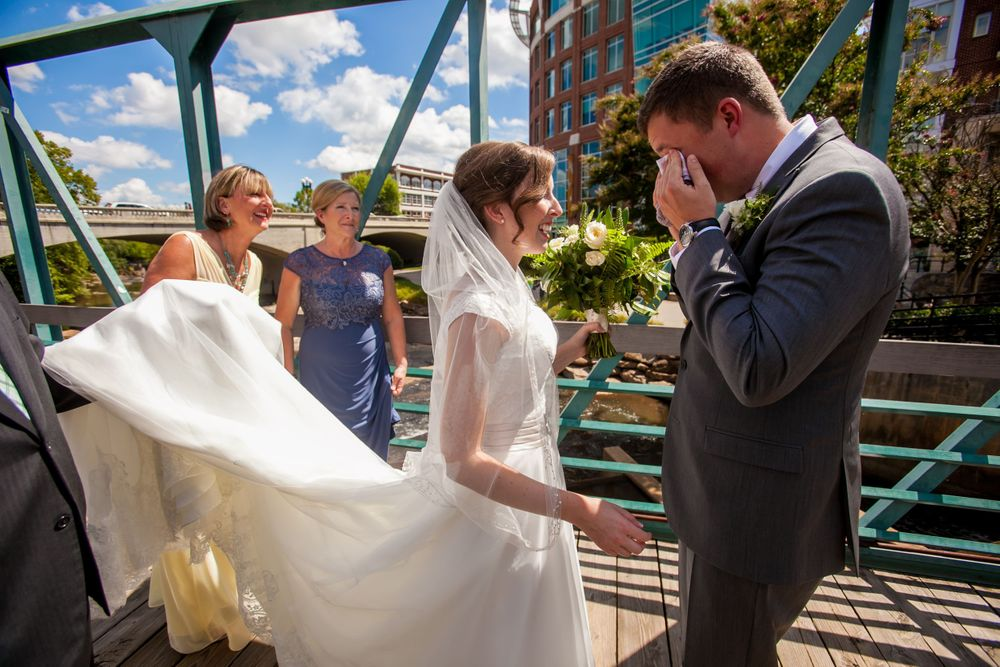 Groom David cries after his first look at his Bride Anna on the Liberty Bridge at Falls Park in Greenville, SC