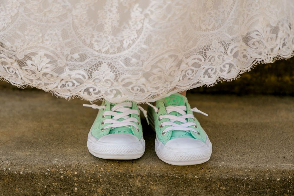 Anna's teal shoes peak out from under her bridal gown before her wedding at Certus Loft Huegonot Mill in Greenville SC