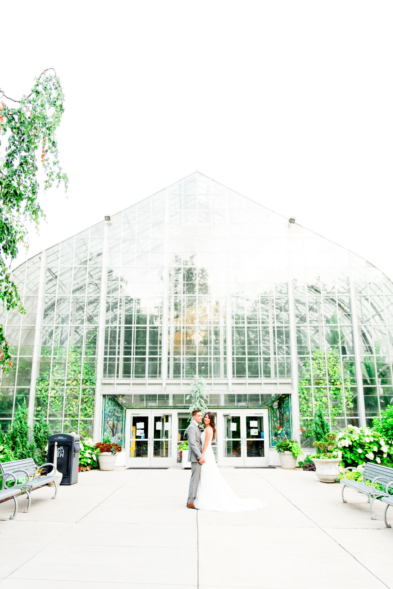 bride and groom hold hands and kiss cheek in front of Krohn Conservatory summer wedding