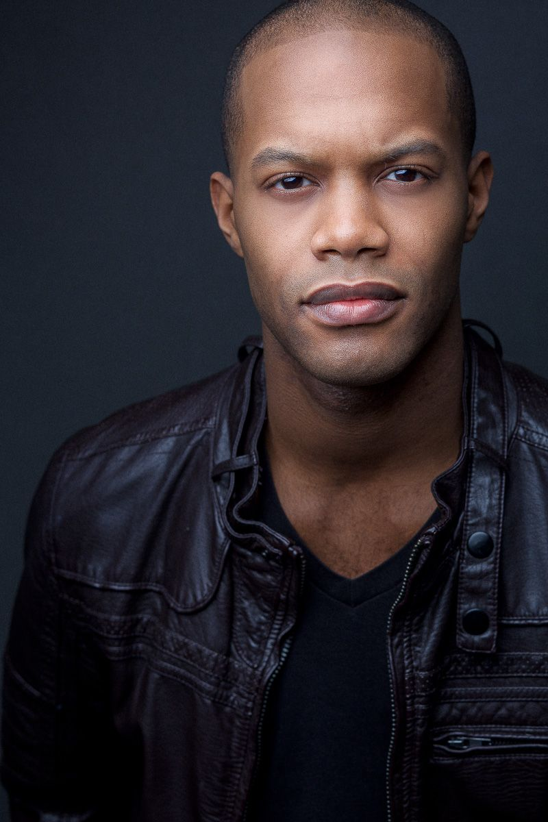 headshots nyc of man in shiny leather jacket again dark background