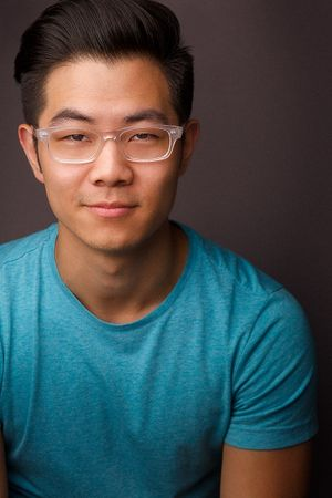 headshots nyc of asian actor in clear rimmed glasses and turquoise tshirt
