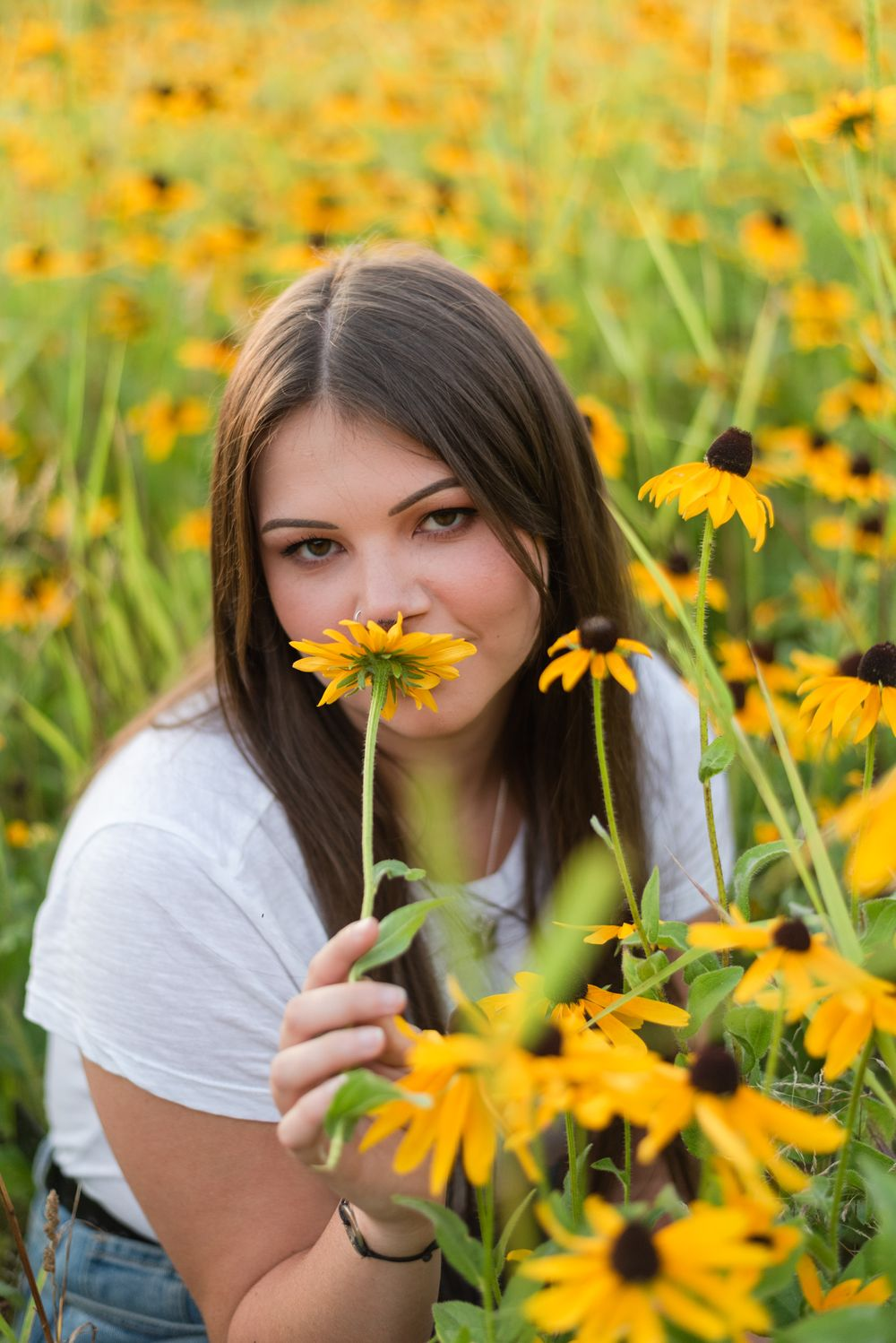 High school senior sitting in flower patch in golden sunlight at Hartwood Acres in Pittsburgh Pennsylvania