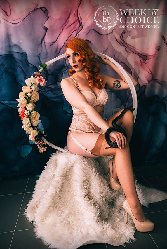 Red head burlesque glamour goddess working her magic in front of the camera with a floral hoop and fur blanket.