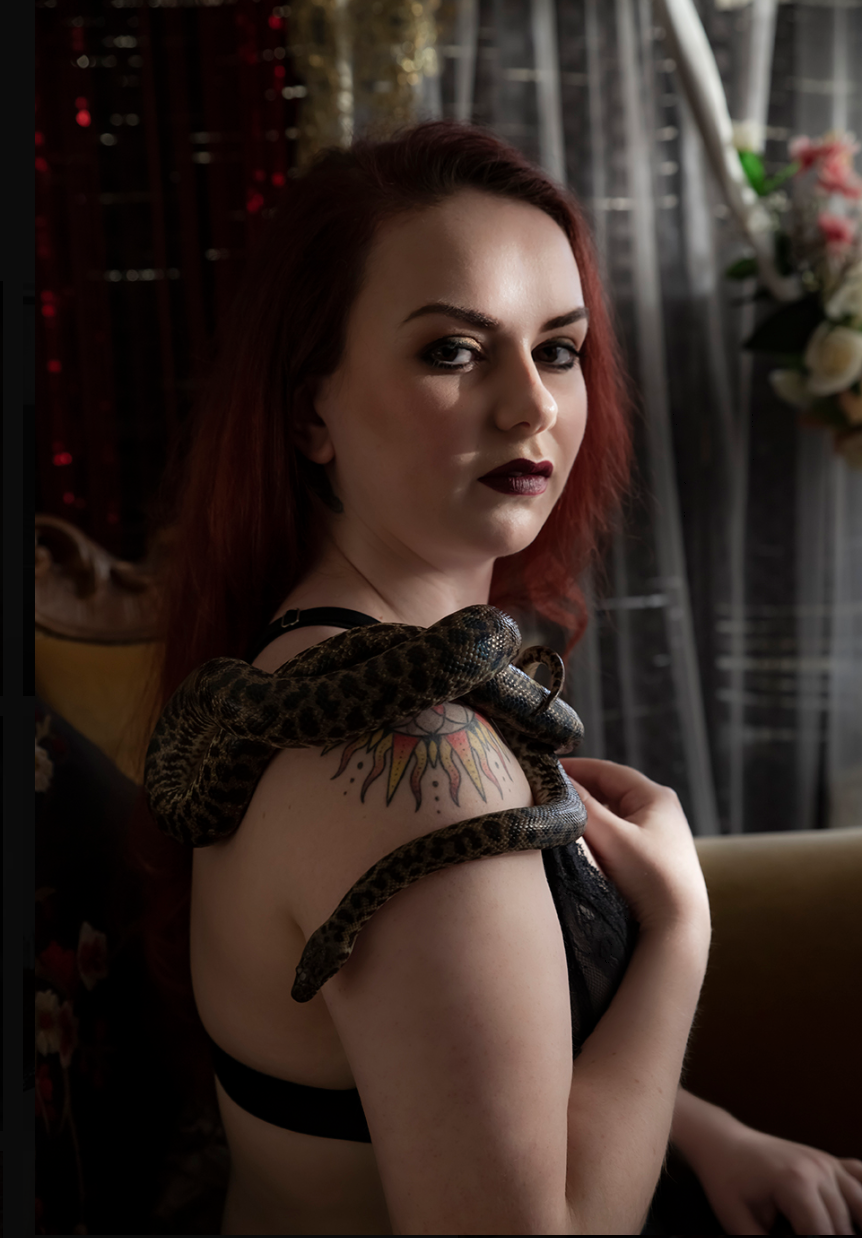 Gothic boudoir model gazing at camera while patting her pet snake draped over her naked shoulder.